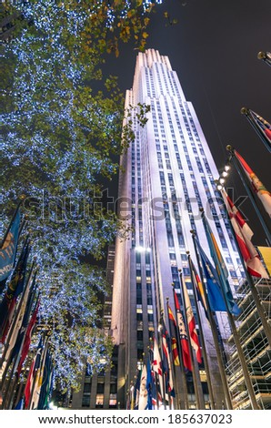 NEW YORK - NOVEMBER 22, 2013: Rockefeller Center by night with international flags and lighting decorations. The complex is made of 19 commercial buildings between 48th and 51st streets in Manhattan. - stock photo