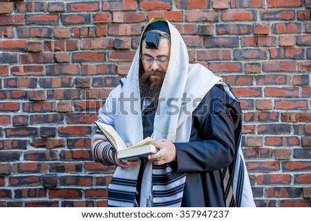 NEW YORK - NOVEMBER 8: Ultra Orthodox Jewish man prays during The Kinus Hashluchim, International Conference of Chabad-Lubavitch Emissaries, in Crown Heights, Brooklyn, NY on November 8, 2015.  - stock photo