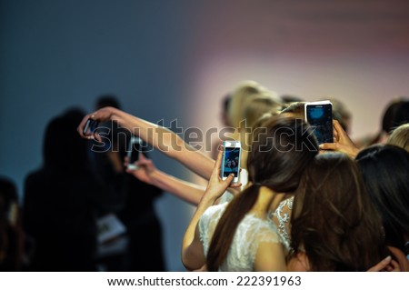 NEW YORK, NY - APRIL 11: Models and guests take pictures on the phones  during the RIVINI Spring 2015 Bridal collection show at on April 11, 2014 in New York City. - stock photo