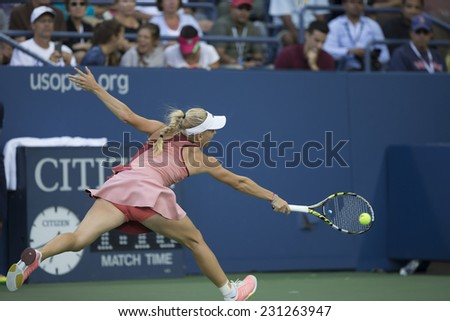 NEW YORK, NY - AUGUST 29, 2014: Caroline Wozniacki of Denmark returns ball during 2nd round match against Andrea Petkovic of Germany at US Open tennis tournament in Flushing Meadows USTA Tennis Center - stock photo