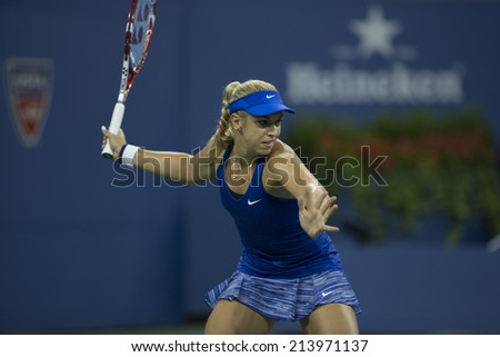 NEW YORK, NY - AUGUST 29, 2014: Sabine Lisicki of Germany returns ball during 2nd round match against Maria Sharapova of Russia at US Open tennis tournament in Flushing Meadows USTA Tennis Center - stock photo