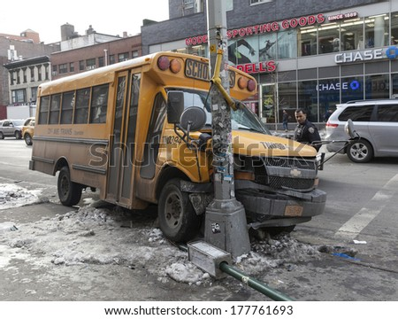 NEW YORK, NY - FEBRUARY 12, 2014: Police officer examines school bus accident on the corner of 6th avenue and 18th street in Manhattan - stock photo