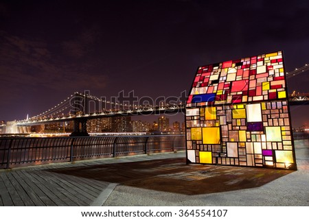 NEW YORK, NY - JULY 14, 2015: To mark the DUMBO Arts Festival the sculptor Tom Fruin has created the Kolonihavehus. It is a colorful house of plexiglass located near the Brooklyn Bridge Park. - stock photo