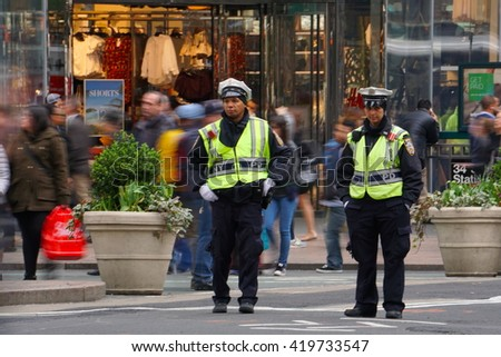 New York, NY - May 10, 2016: Two NYPD traffic police officers patrol Herald Square in midtown Manhattan during the evening commute - stock photo
