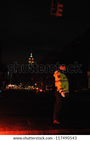 NEW YORK, NY - NOVEMBER 1: NYPD directs traffic on Sixth Ave in the West Village with Empire State building in background during the blackout caused by Hurricane Sandy on Nov 1st 2012 in New York. - stock photo