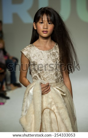NEW YORK, NY - OCTOBER 19: A model walks the runway during the Ruum preview at petitePARADE / Kids Fashion Week at Bathhouse Studios on October 19, 2014 in New York City. - stock photo