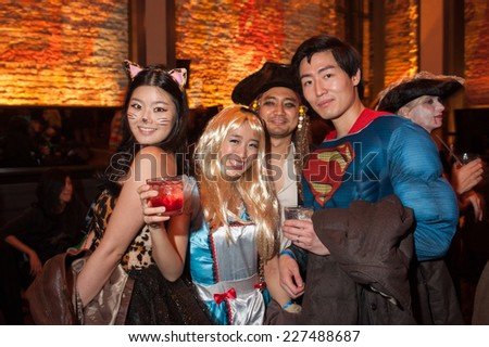 NEW YORK, NY - OCTOBER 31: Guests in mascarade costumes posing at The Fashion Party during Halloween event at the Venue 409 on October 31, 2014 in New York City.  - stock photo