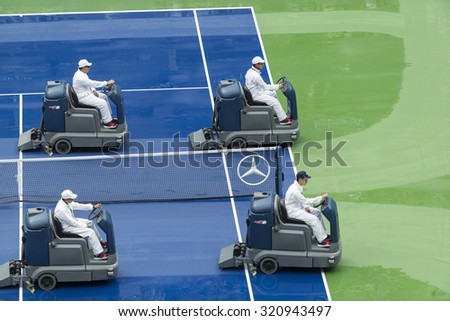 New York, NY - September 13, 2015: Crew drying court after rain at final of US Open Championship between Roger Federer of Switzerland & Novak Djokovic of Serbia at Ash stadium - stock photo