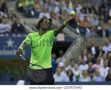 NEW YORK, NY - SEPTEMBER 4, 2014: Gael Monfils of France serves ball during quarterfinal match against Roger Federer of Switzerland at US Open championship in Flushing Meadows USTA Tennis Center - stock photo