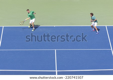 NEW YORK, NY - SEPTEMBER 7, 2014: Marcel Granollers & Marc Lopez of Spain return ball during men doubles final match against Bryan brothers of USA at US Open championship in Flushing Meadows - stock photo