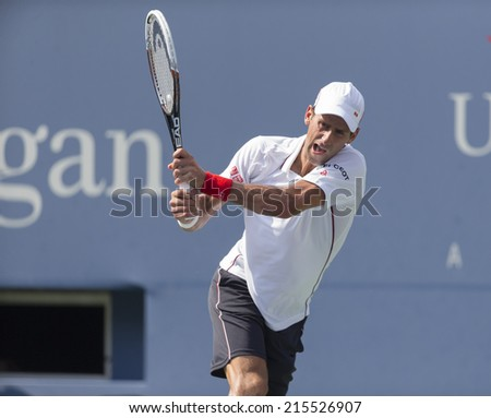 NEW YORK, NY - SEPTEMBER 6, 2014: Novak Djokovic of Serbia returns ball during semifinal match against Kei Nishikori of Japan at US Open championship in Flushing Meadows USTA Tennis Center - stock photo