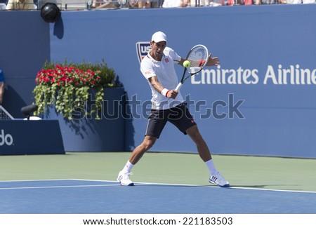 NEW YORK, NY - SEPTEMBER 6, 2014: Novak Djokovic of Serbia returns ball during semifinal match against Kei Nishikori of Japan at US Open championship in Flushing Meadows USTA Tennis Center - stock photo