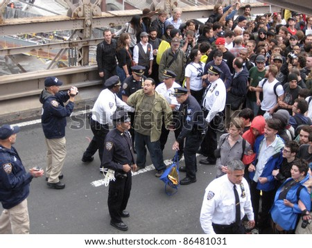 NEW YORK - OCT 1: Police arrest an unidentified man on the roadway of the Brooklyn Bridge, October 1, 2011 in New York City. Hundreds of people were arrested at an Occupy Wall Street protest march. - stock photo