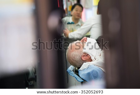 New York, October 21, 2015 - eldery men getting hot shave in the barber shop - stock photo