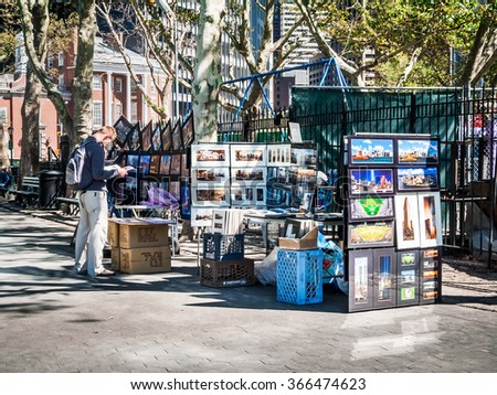 NEW YORK-SEPTEMBER 29: A young man looks through a book at an art sale stand in Battery Park on September 29 2005 in New York City. - stock photo