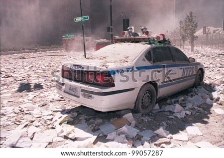 NEW YORK - SEPTEMBER 11: Ash covers a NYPD vehicle as it lies near the area known as Ground Zero after the collapse of the Twin Towers on September 11, 2001 in New York City. - stock photo