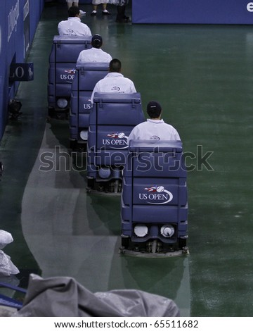 NEW YORK - SEPTEMBER 13: Crew members clean the court after the rain during final match of US Open Tennis Championship between Rafael Nadal of Spain and Novak Djokovic of Serbia on Sep 13, 2010 in NYC - stock photo