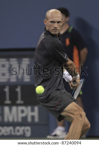 NEW YORK - SEPTEMBER 03: Nikolay Davydenko of Russia returns ball during 3rd round match against Novak Djokovic of Serbia at USTA Billie Jean King National Tennis Center on September 03, 2011 in New York City, NY. - stock photo