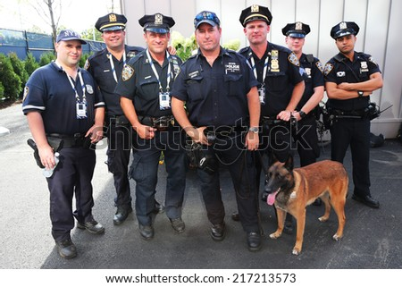 NEW YORK - SEPTEMBER 7: NYPD transit bureau K-9 police officers and K-9 dog providing security at National Tennis Center during US Open 2014 on September 7, 2014 in New York  - stock photo