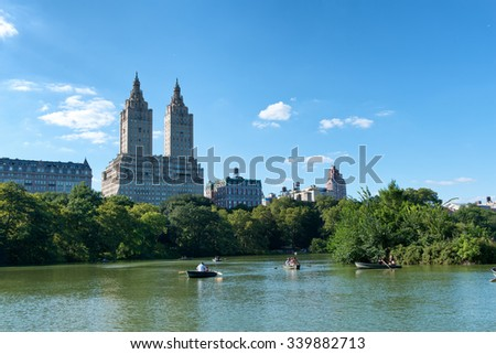 NEW YORK - SEPTEMBER 06: People Enjoying the Day Rowing Boats on Lake in Central Park with View of San Remo Building on Beautiful Sunny Day, New York City, New York, USA. September 06 2015. - stock photo