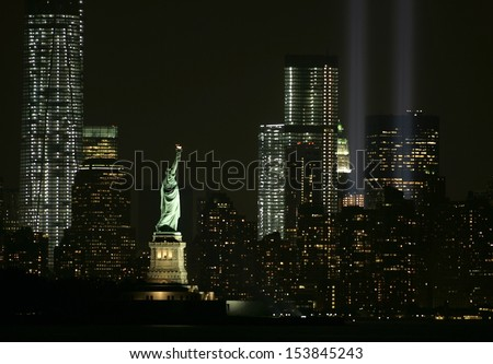 NEW YORK - SEPTEMBER 11: The Statue of Liberty is illuminated as the Tribute in Light installation is seen in lower Manhattan on September 11, 2013 in New York City. - stock photo