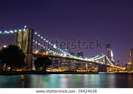 New York Skyline at night with Brooklyn Bridge - stock photo