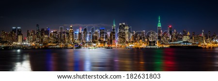 New York skyline panorama by night, taken in front of the 42nd street canyon. Empire State Building is lit in green to honor Saint Patrick's Day. - stock photo