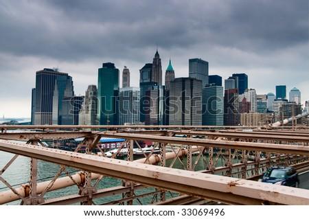 New York skyline viewed from Brooklyn Bridge with a dramatic dark sky - stock photo