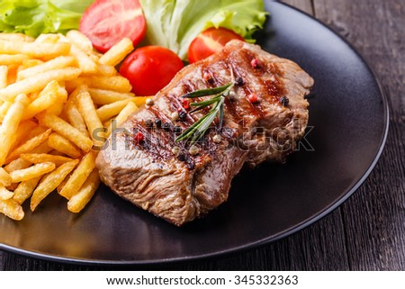 New York steak with french fries and salad. - stock photo