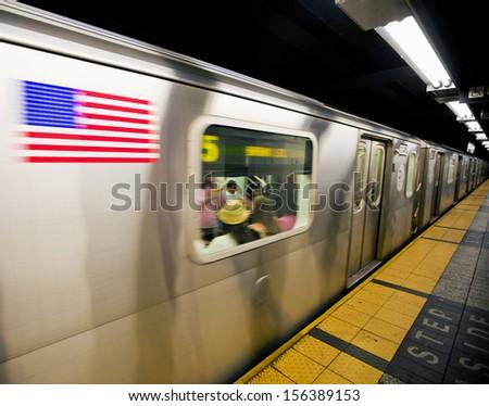 New York subway train moving through station - stock photo