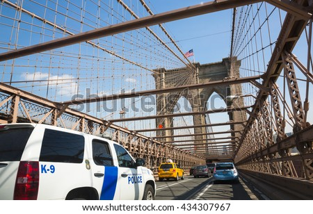 NEW YORK, USA - Apr 27, 2016: Police car on Brooklyn Bridge. Brooklyn Bridge is a hybrid cable-stayed suspension bridge in New York City and is one of the oldest bridges of either type in the US - stock photo