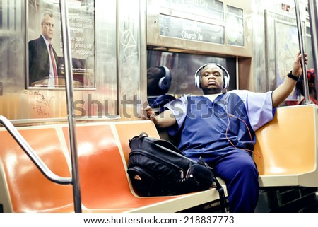 NEW YORK. USA - AUGUST 21, 2012: American African man listening to music in subway on August 21, 2012, New York, USA - stock photo
