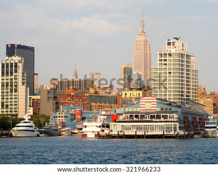 NEW YORK,USA - AUGUST 17,2015 : Piers and boats along the Manhattan coast with the Empire State Building on the background - stock photo