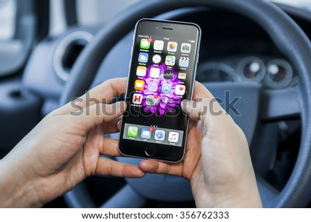 New York, USA - December 21, 2015:  Female  using her space grey color iPhone 6 smart phone in the car. - stock photo