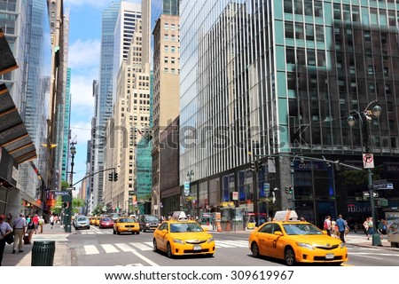 NEW YORK, USA - JULY 4, 2013: People ride yellow taxi cabs along 42nd Street in New York. As of 2012 there were 13,237 yellow taxi cabs registered in New York City. - stock photo