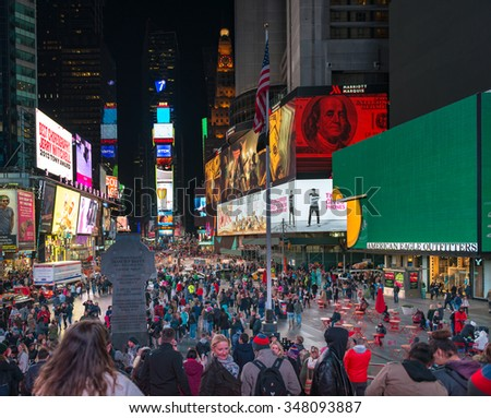 NEW YORK,USA-JULY 4,2015:Times Square at night:Times Square is a major commercial intersection and neighborhood in Midtown Manhattan.The landmark is brightly adorned with billboards and advertisements - stock photo