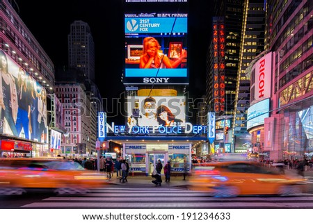 NEW YORK, USA - MARCH 16: Symmetrical composition of New York Police Department on Times Square at night with neon lights, with people and taxis, yellow cabs, on March 16, 2014 in New York, USA. - stock photo