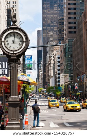 NEW YORK, USA, MAY 12th, 2013. New York urban city life with taxis passing by 5th avenue and a big street clock. Taken in the morning of May 12th 2013.  - stock photo