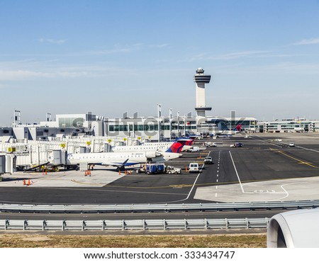 NEW YORK, USA - OCT 20, 2015: Air Traffic Control Tower and Terminal 4 with Delta Air planes at the gates in JFK Airport in NY. 1963 the airport was rededicated John F. Kennedy International Airport. - stock photo