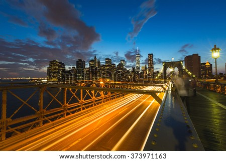 New York view at dusk, with traffic trails on Brooklyn Bridge and Manhattan skyline on background. Travel and transportation concepts on this postcard style picture. - stock photo
