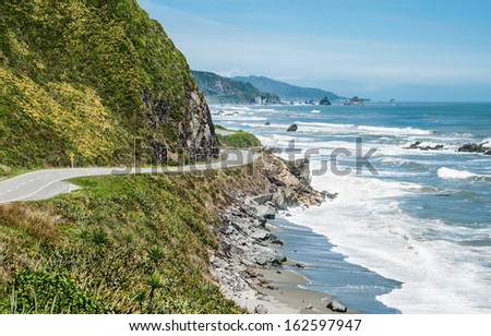 New Zealand Coastal Highway:  A scenic road winds along the western shore of New Zealand's South Island.  - stock photo
