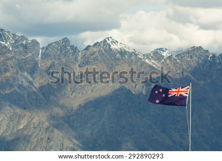 New Zealand Flag waving on top of the pole in front of the Remarkables - stock photo