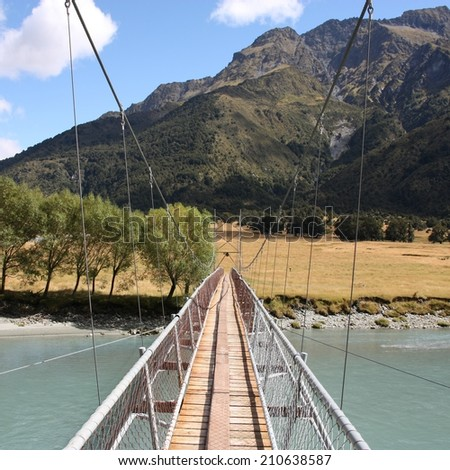 New Zealand. Suspended wire bridge - river crossing on a tourist trail in Mount Aspiring National Park. Square composition. - stock photo