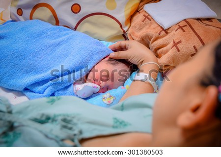 Newborn and Mother in hospital after giving birth (focused on newborn) - stock photo