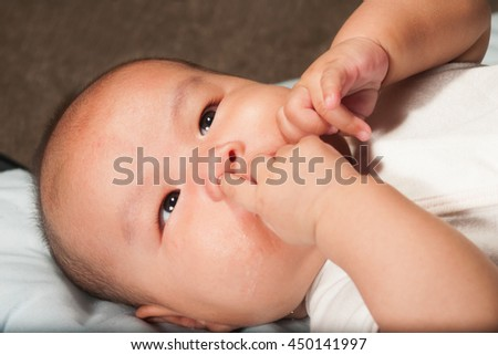 Newborn Asian baby girl lying on a bed. - stock photo