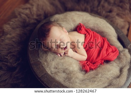 Newborn baby boy in a bowl - stock photo