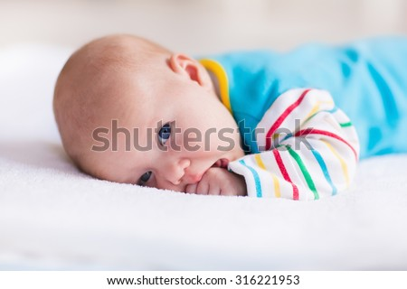 Newborn baby boy in bed. New born child playing on a white blanket. Children sleep. Bedding for kids. Infant napping in bed. Healthy little kid shortly after birth. Clothing for kids. - stock photo