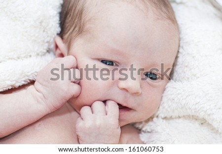 newborn baby boy lying on a blanket with his eyes open  - stock photo