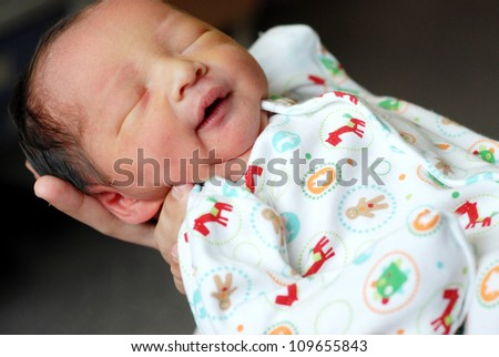 newborn baby boy on the father's hand - stock photo
