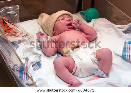 Newborn baby boy resting in hospital post-delivery room - stock photo